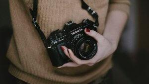 Zdjęcie przedstawia rękę kobiety podtrzymującą aparat fotograficzny zawieszony na jej szyi