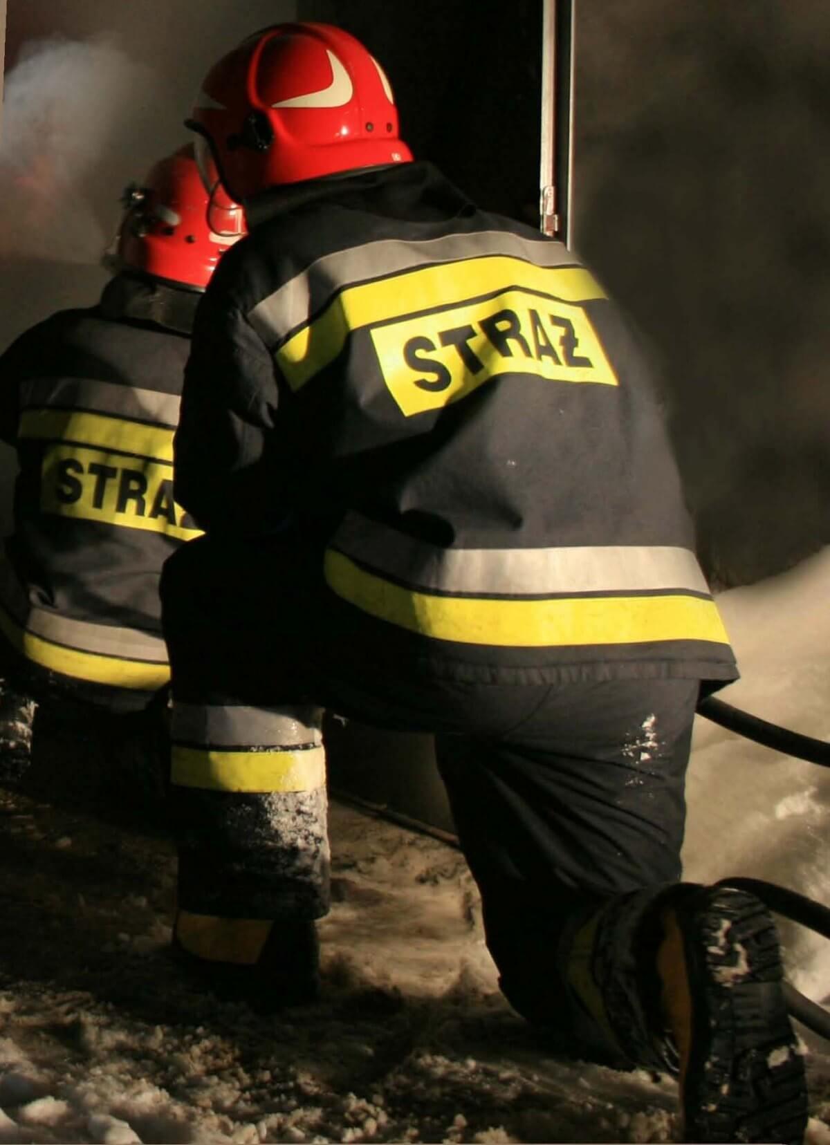 Strażak podczas akcji klęczący tyłem na prawej nodze, w czerwonym hełmie na głowie, w czarnym mundurze z napisem na plecach straż, a w tle za nim drugi strażak