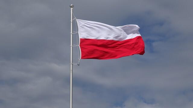 Flaga biało-czerwona wzniesiona na maszcie, powiewająca, na tle nieba