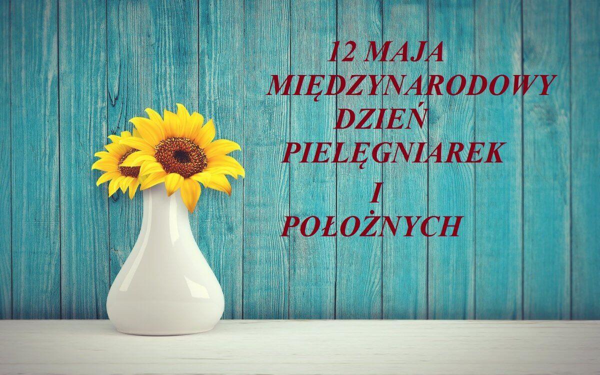 Na tle turkusowej ściany po prawej stronie napis 12 Maja Międzynarodowy Dzień Pielęgniarek i Położnych, po lewej w białym wazonie, na białym stole dwa żółte słoneczniki