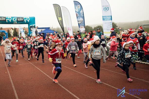 Zdjęcie przedstawia zawodników - dzieci w zawodach biegowych Bieh Mikołajkowy na stadionie lekkoatletycznym w Policach
