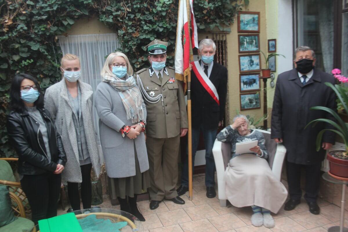 Zdjęcie przedstawia Krystynę Łanowską oraz stojących obok niej po lewej stronie Burmistrza Polic, po prawej stronie Wicestarostę Polickiego oraz przedstawicieli Związku Kombatantów Rzeczypospolitej Polskiej i Byłych Więźniów Politycznych