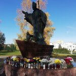 Figura św. Jana Pawła II w Policach przyozdobiona chryzantemami