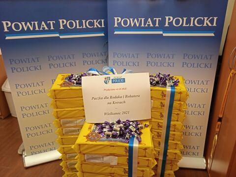 Paczki cukierków w trzech kolumnach na tle roll upów z napisem POWIAT POLICKI przygotowane do przekazania na akcję Paczka dla Rodaka i Bohatera na Kresach-Wielkanoc 2021