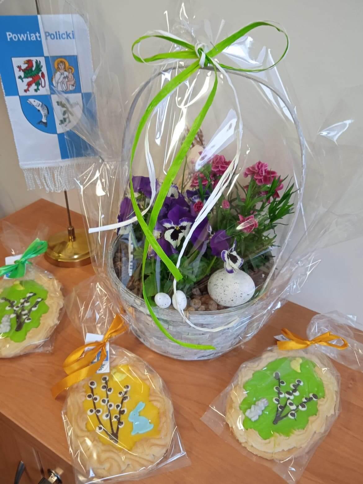 Wielkanocny kosz oraz ozdoby świateczne w postaci 3 kolorowych ciast typu mazurek.