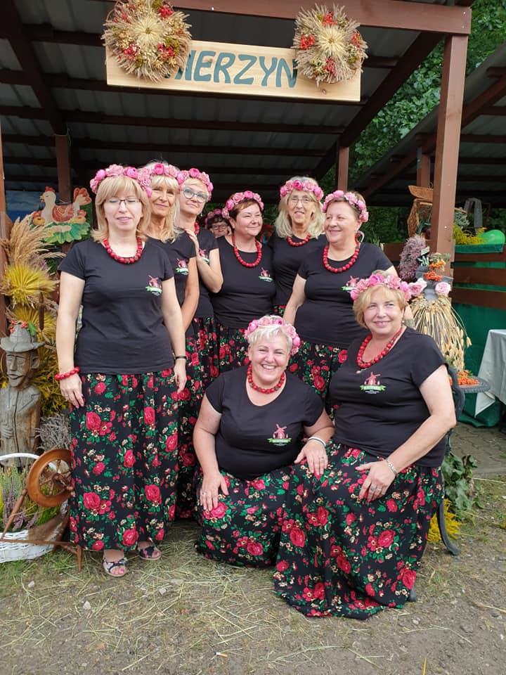 Panie z koła Gospodyń Wiejskich Mierzynianki na tle swojego stoiska podczas dożynek w Dobrej, ubrane w czarne koszulki i czarne spódnice w czerwone kwiaty, a na głowach kolorowe wianki