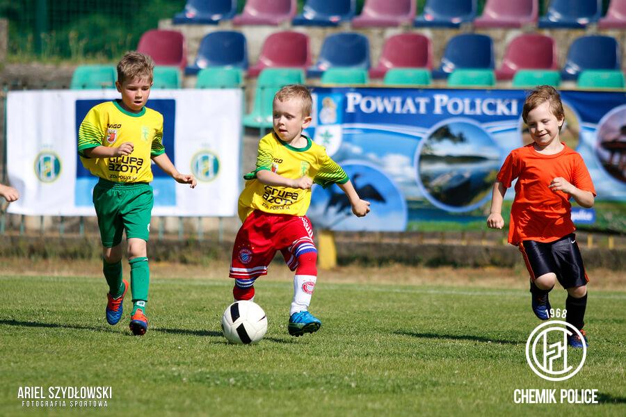 Trzech chłopców grających w piłke na murawie