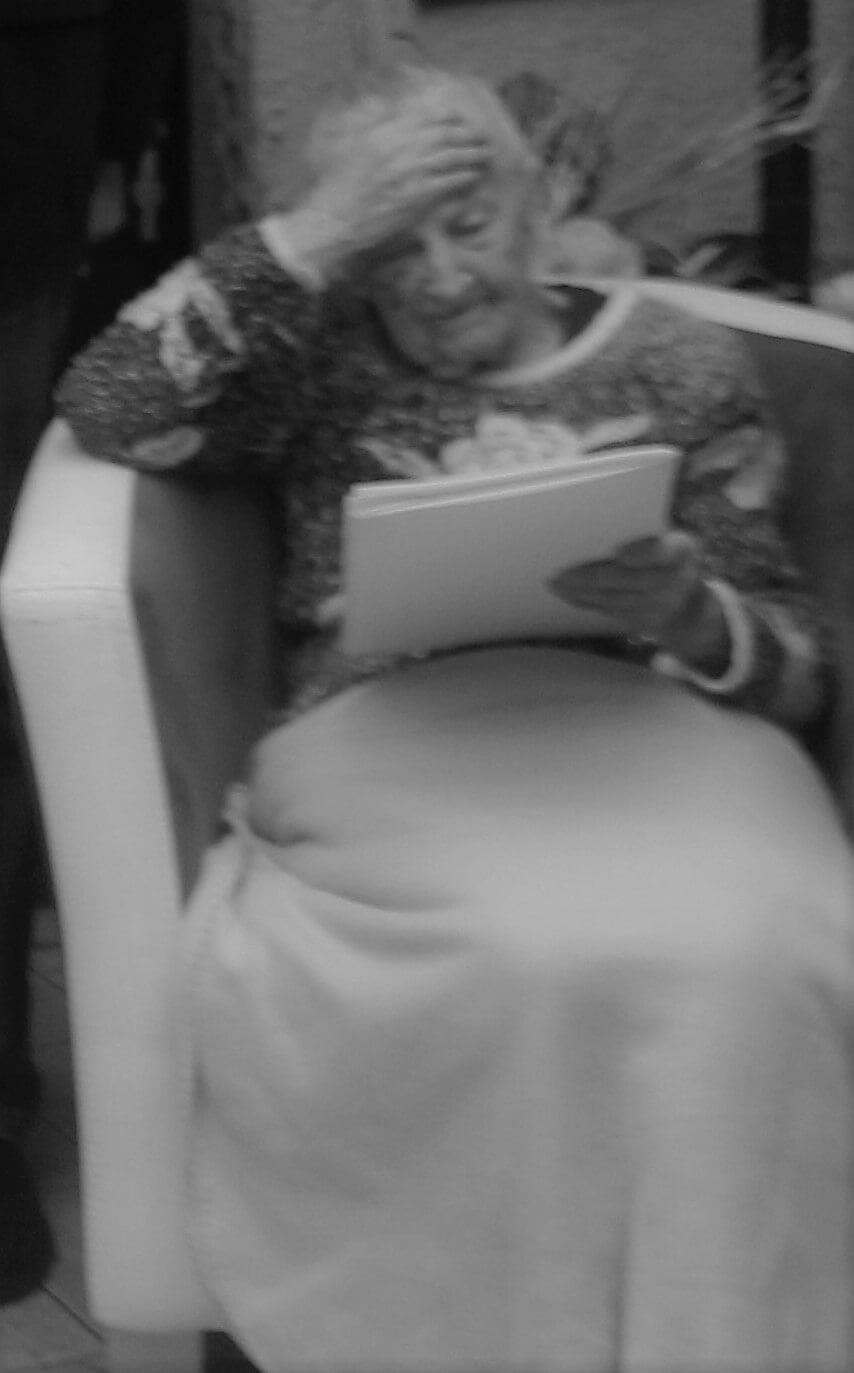Krystyna Łanowska siedząca w fotelu, okryta kocem i podpierająca głowę prawą ręką
