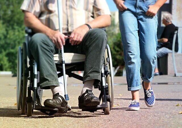 Na pierwszym planie męźczyzna siedzący na wózku inwalidzkim, trzymający w prawej dłoni laskę, a obok w niebieskich jeansach i tenisków idąca kobieta