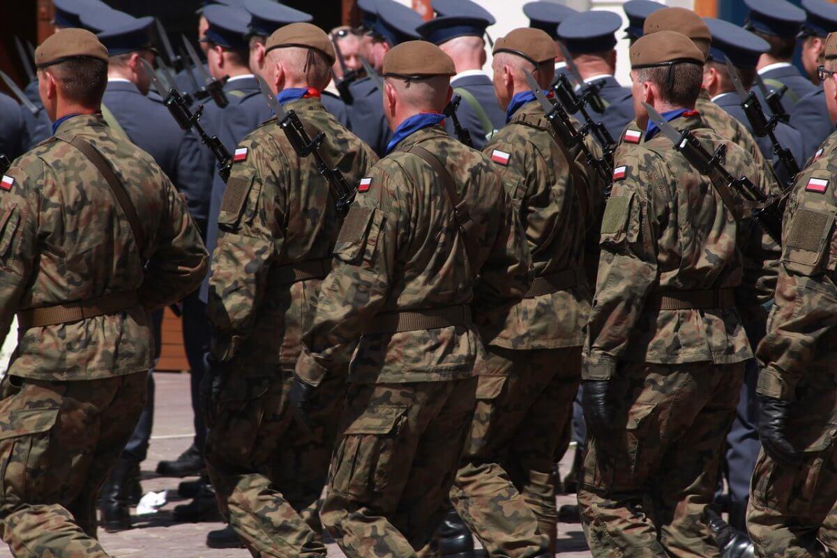 Klęczący żołnierze w mundurach, obróceni tyłem