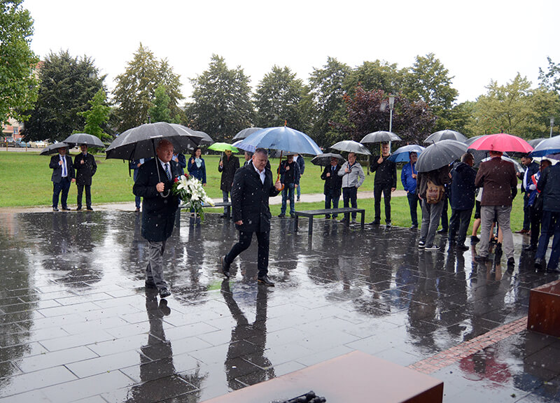 Przewodniczący Rady Powiatu w Policach Cezary Arciszewski wraz z Adamem Pacholikiem Prezesem Trans-Net składają kwiaty przed pomnikiem Ludziom Solidarności w Policach
