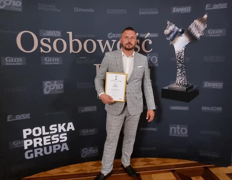 Pan Piotr Kołacki trzymający w prawej dłoni dyplom w ramce Tytuł Osobowości Roku Pomorza Zachodniego 2020, na tle ścianki w kolorze ciemnego granatu z napisami Osobowość, Polska Press Grupa i grafiką statuetki Osobowości Roku