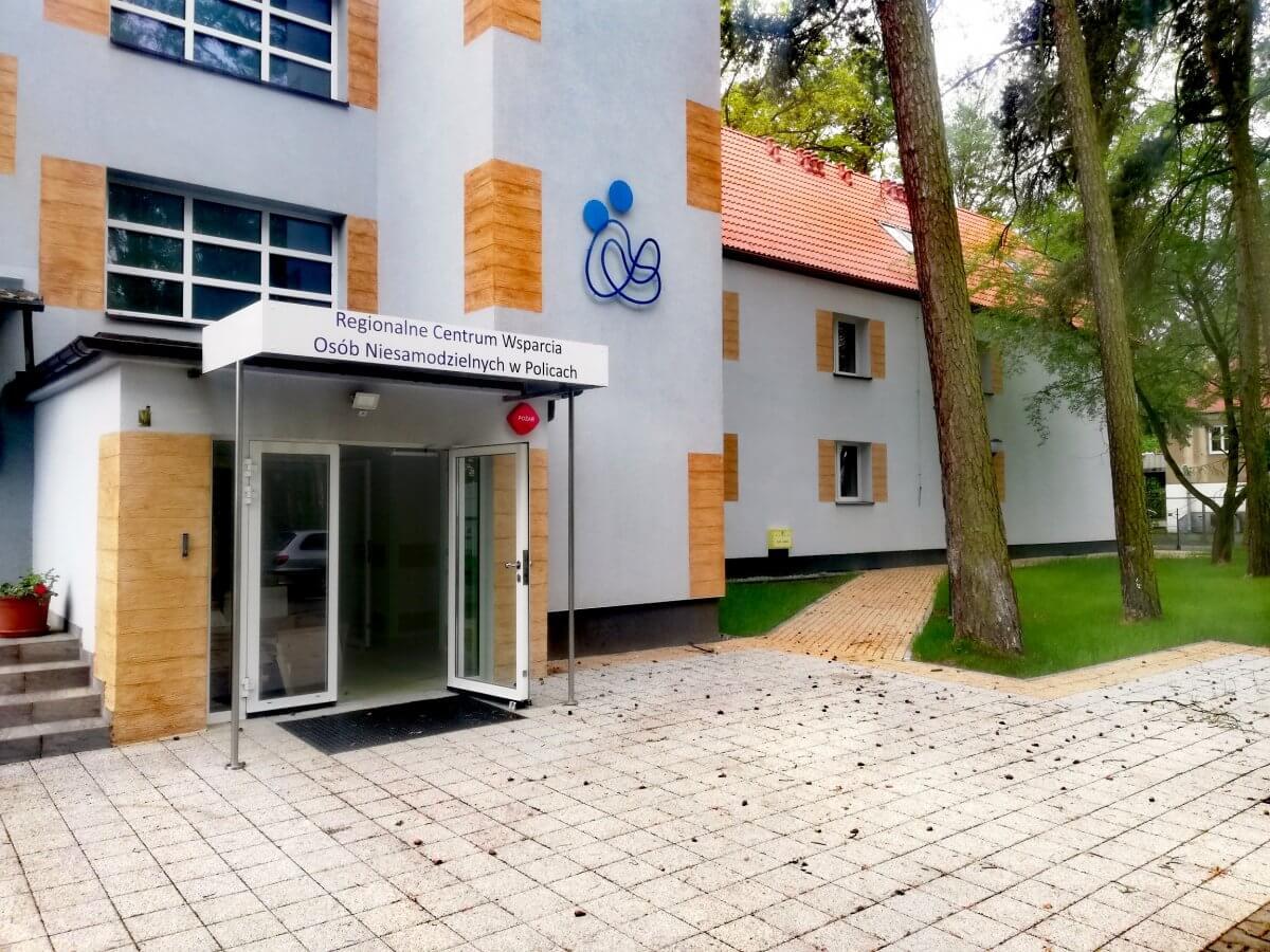 Biało-pomarańczowy budynek Regionalnego Centrum Wsparcia Osób Niesamodzielnych w Policach