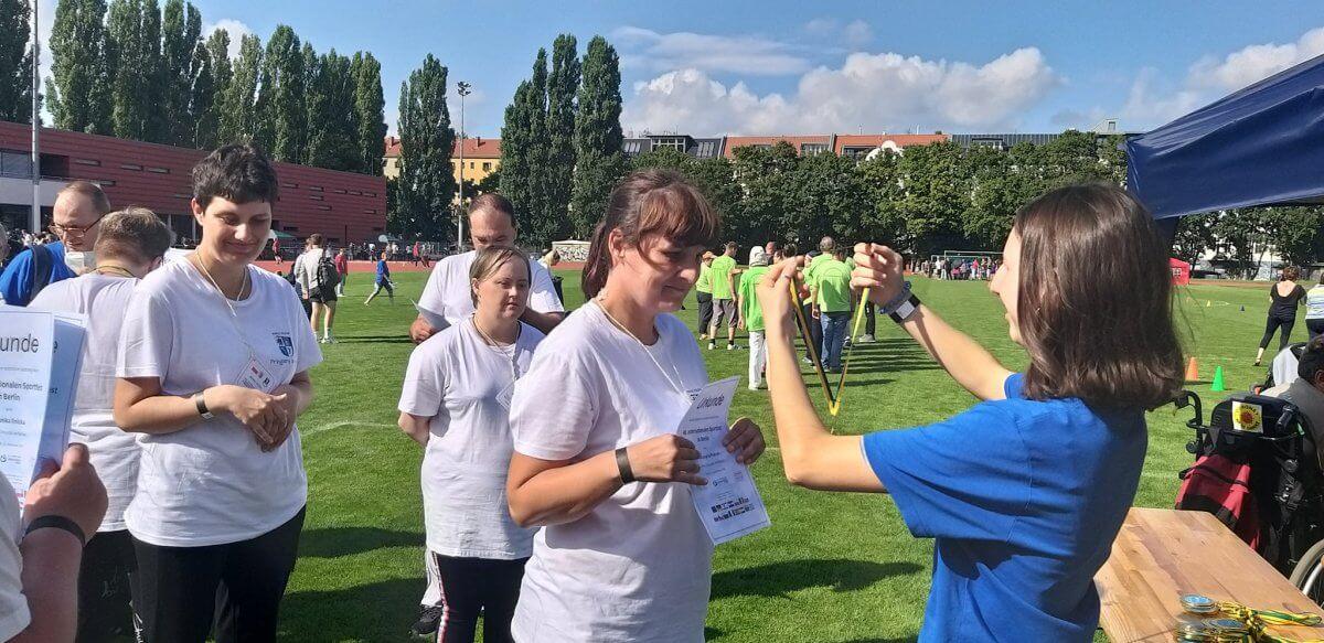Uczestnik WTZ w Policach odbiera pamiątkowy medal za udział w zawodach