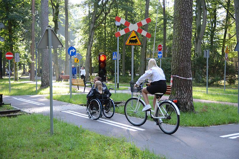 Osoby na wózkach inwalidzkich i na rowerze korzystają z miasteczka ruchu drogowego w SOSW nr 1 w Policach
