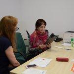 Senior z Powiatu Polickiego przy biurku wraz ze specjalistą rozwiązuje testy na tablecie
