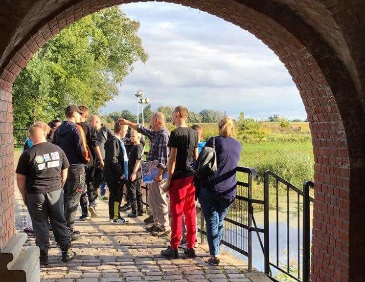 Uczestnicy projektu Dalsze podróże po świecie w trakcie zwiedzania, stoją na moście nad rzeką