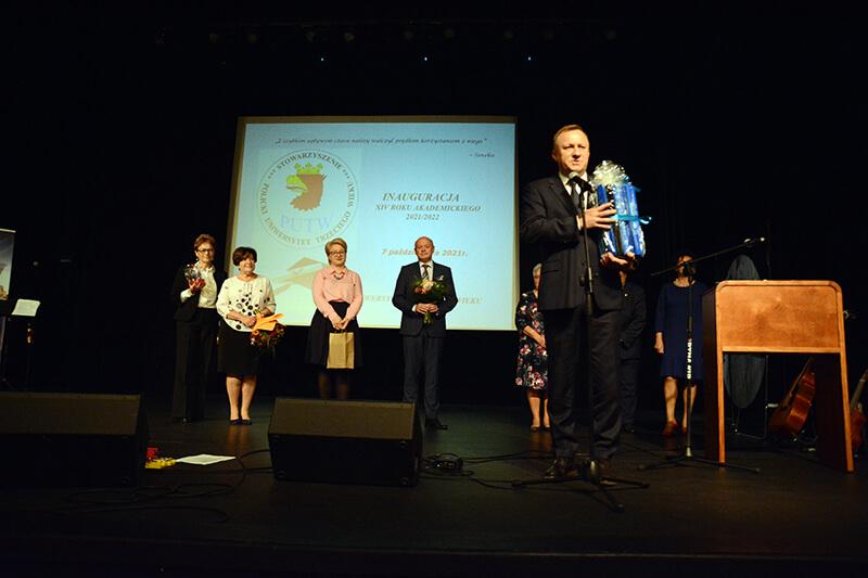 Starosta Policki Andrzej Bednarek przemawia na scenie, a w tle stoją Przewodniczący Rady Powiatu w Policach Cezary Arciszewski, Wicestarosta Policki Joanna Napiwodzka oraz inni goście