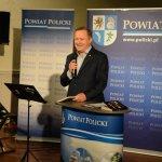 Starosta Policki Andrzej Bednarek stojący przy mównicy z grafiką Powiat Policki, witający wszystkich przybyłych na uroczystą premierę książki. w tle grafika Powiatu Polickiego z herbem na niebieskim tle.