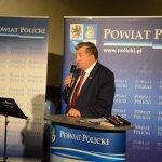 Burmistrz Polic Władysław Diakun stojący przy mównicy z grafiką Powiat Policki, witający wszystkich przybyłych na uroczystą premierę książki. w tle grafika Powiatu Polickiego z herbem na niebieskim tle.