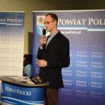 Bartosz Sitarz stojący przy mównicy z grafiką Powiat Policki, wygłaszający swoją prelekcję. w tle grafika Powiatu Polickiego z herbem na niebieskim tle.