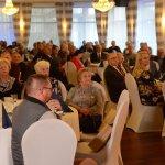 Zbliżenie gości, siedzących przy okrągłych stołach i słuchających wystąpień.