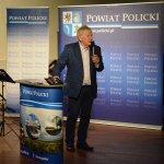 Wiesław Gaweł stojący przy mównicy z grafiką Powiat Policki, wygłaszający swoją prelekcję. w tle grafika Powiatu Polickiego z herbem na niebieskim tle.