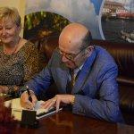"""Stefan Marszałek autor książki pt.""""Oni byli pierwsi"""" siedzący na skórzanej sofie, podpisujący swoją książkę siedzącej obok pani"""
